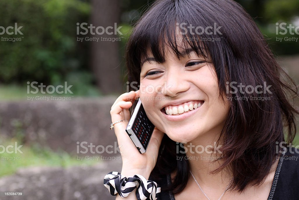 Japanese girl laughing on the phone stock photo