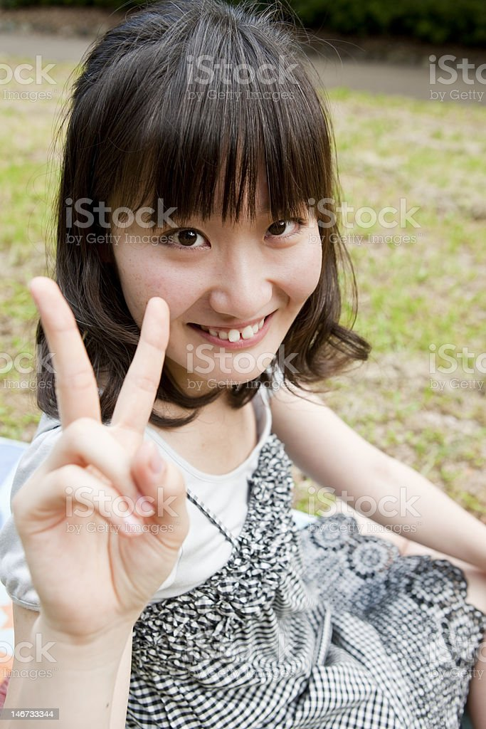 Japanese girl makes a peace sign royalty-free stock photo