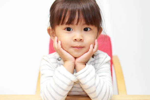 japanese girl resting her chin in her hands (3 years old) - mano sul mento foto e immagini stock