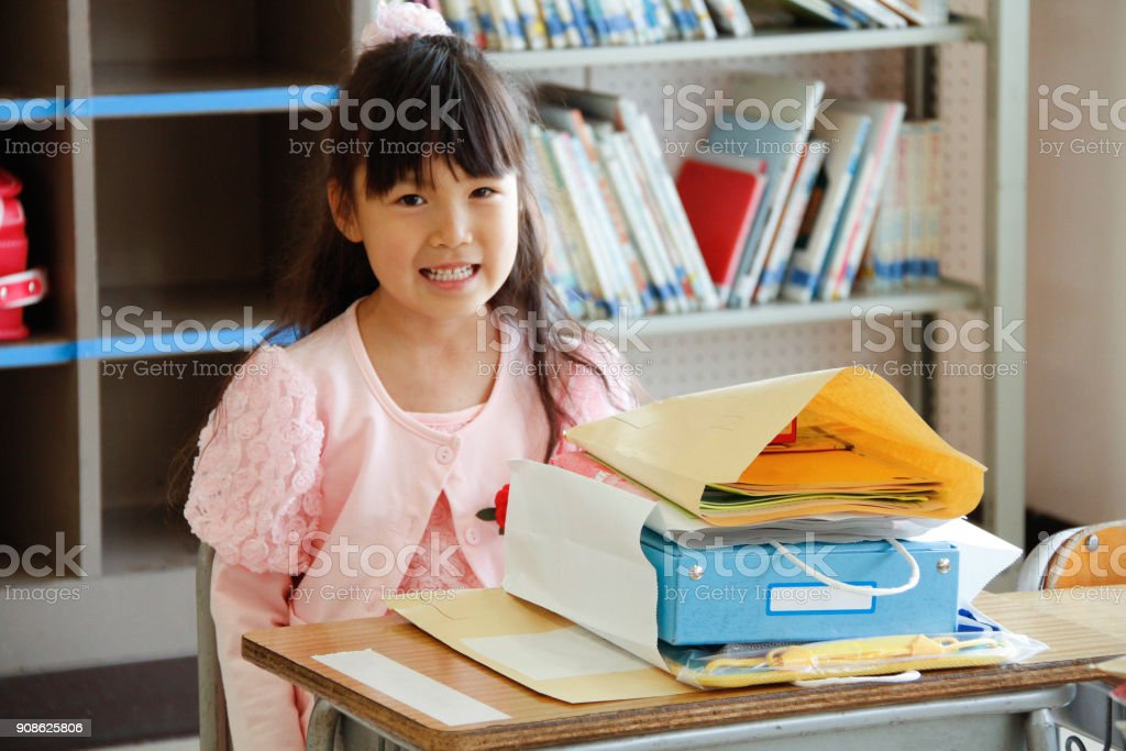 Japanese girl siting at desk with books in class room in elementary school stock photo