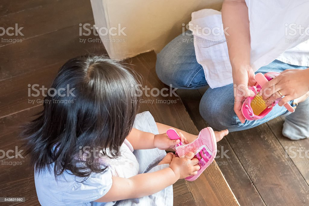 Japanese Girl Toddler Putting on Shoe, Mother Holding Other Shoe stock photo