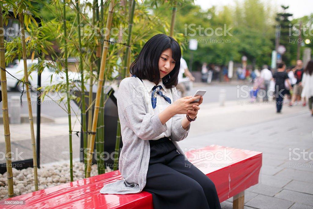 Japonés Chica con teléfono inteligente escribiendo mensaje foto de stock libre de derechos