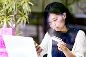 istock Japanese girl using her smartphone and credit card to make an online payment 882830680