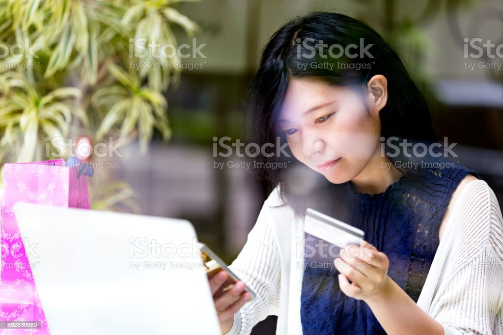 Japanese girl using her smartphone and credit card to make an online payment stock photo