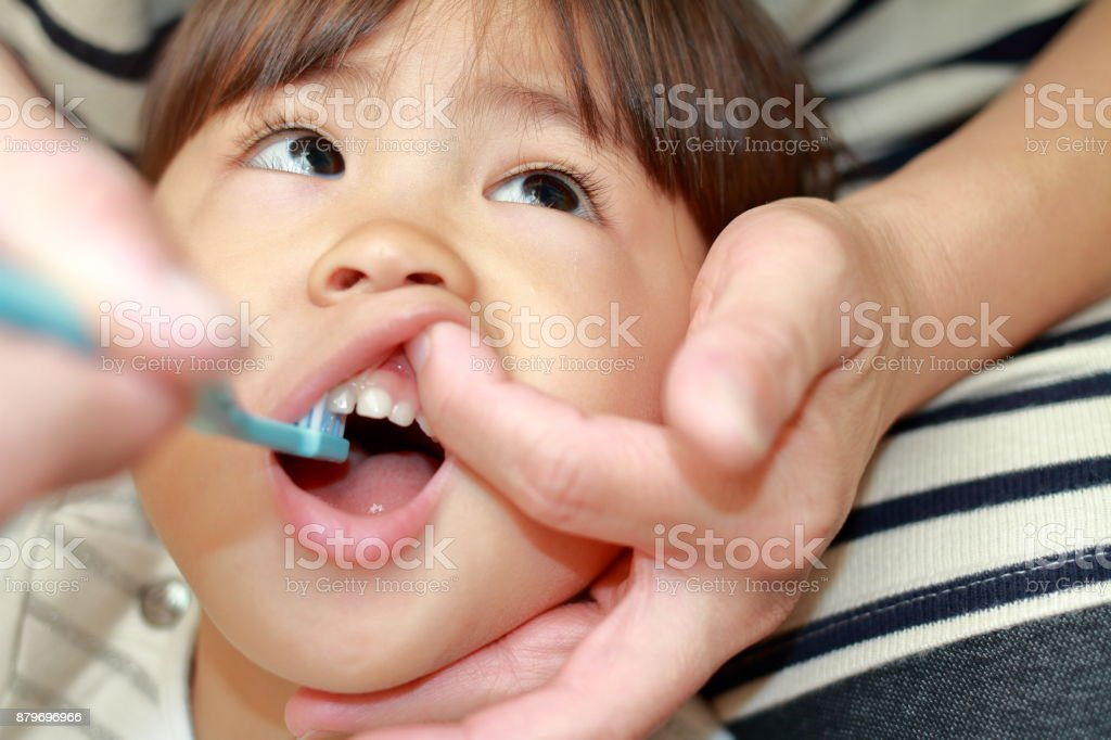 Japanese girl whose teeth are brushed by her mon (3 years old) stock photo