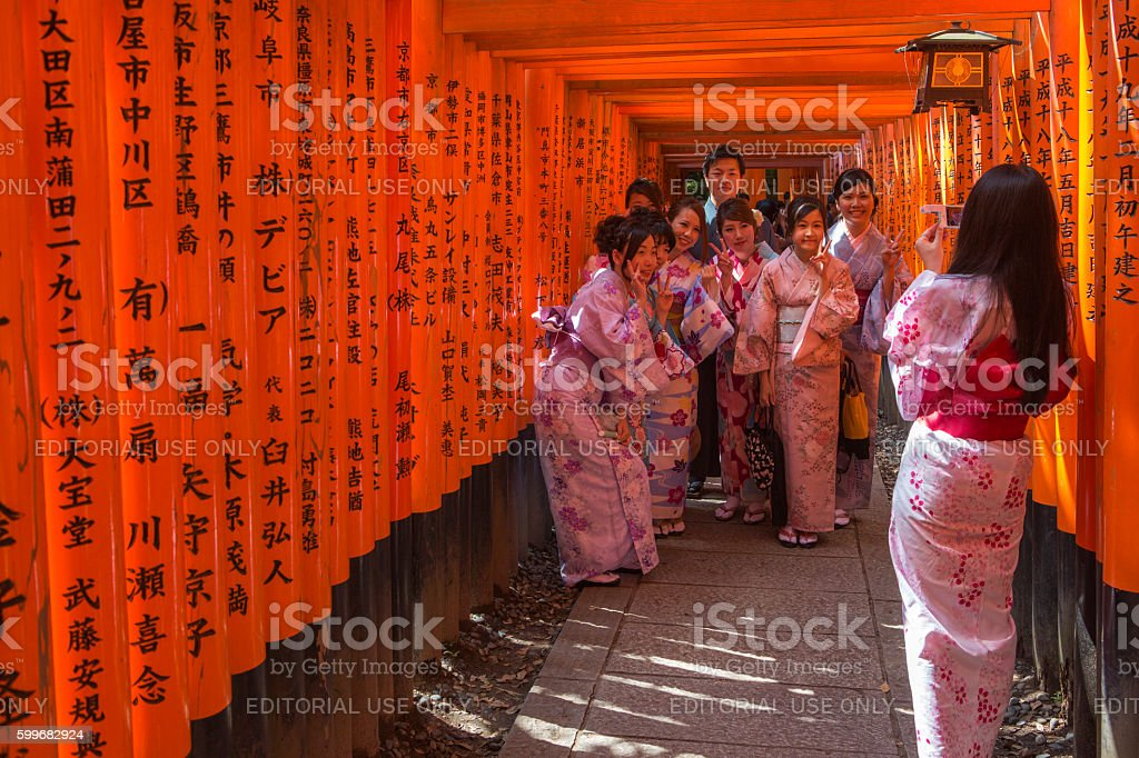japanese girls posing in gates of Fushimi-Inari temple  kyoto japan stock photo