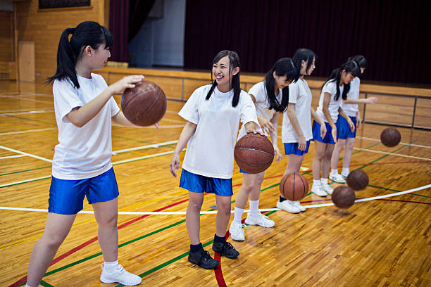 Japanese girls practising basketball in the school gymnasium Japanese girls practising basketball in the school gymnasium. japanese school girl stock pictures, royalty-free photos & images