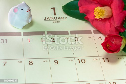 Japanese greeting card with Tsubaki flower called also the rose of winter and cute rat figurine for the 2020 year of the mouse on a Japanese calendar open on January page.
