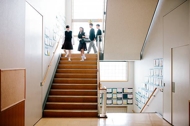 Japanese high school. Four students down a staircase, front view stock photo