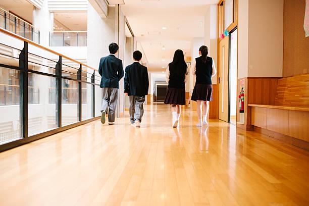 Japanese high school. Four students walk through corridor, rear view stock photo