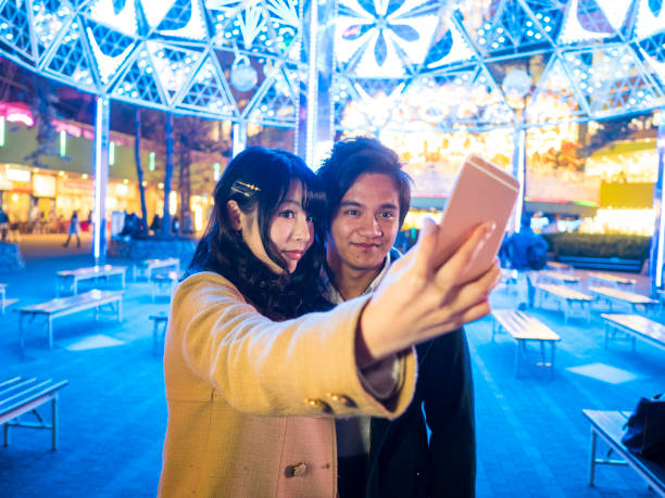 A Japanese high school girl is taking self photos with her boyfriend. stock photo