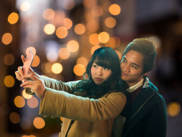 A Japanese high school girl takes a picture with her boyfriend. stock photo
