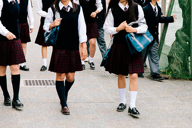 Japanese high school. School children walk outside, unrecognisable, school uniform stock photo