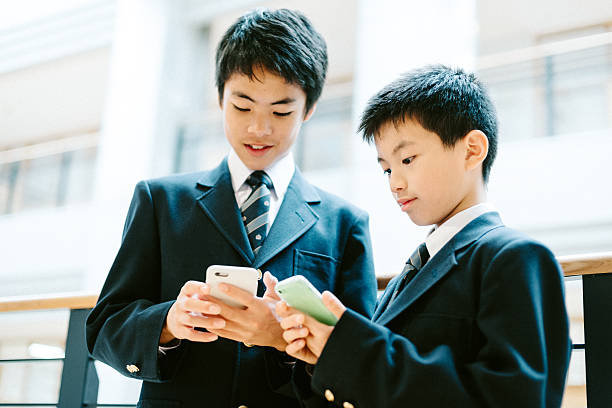 日本の学校の学生の学校でスマートフォンを使用して - 制服 ストックフォトと画像