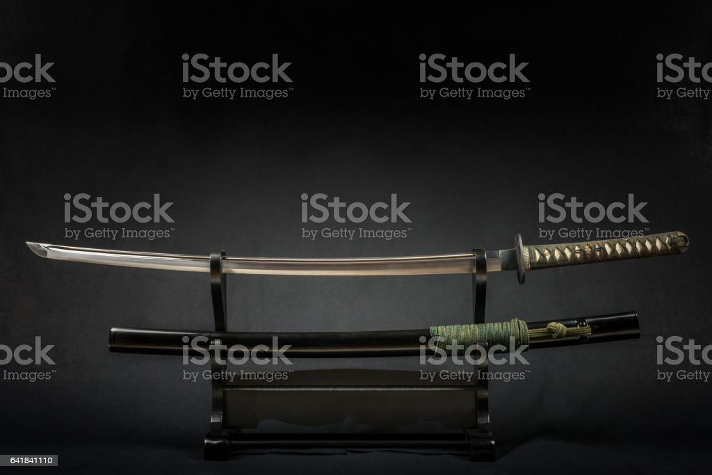 Japanese iaido sword in black wooden stand and black background. stock photo