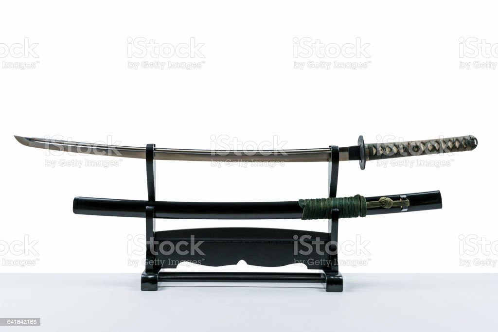Japanese iaido sword in black wooden stand and white background. stock photo