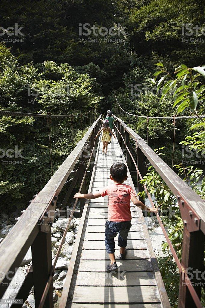 Bambini a piedi sul ponte giapponese foto stock royalty-free
