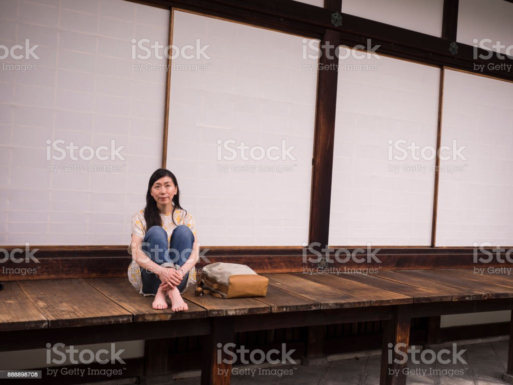 Japanese lady sitting on the bench in the temple. stock photo