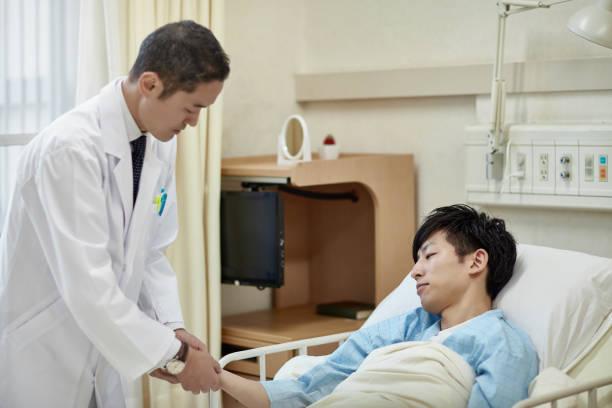 男性患者と相互作用する日本人男性医師 - 病棟 ストックフォトと画像