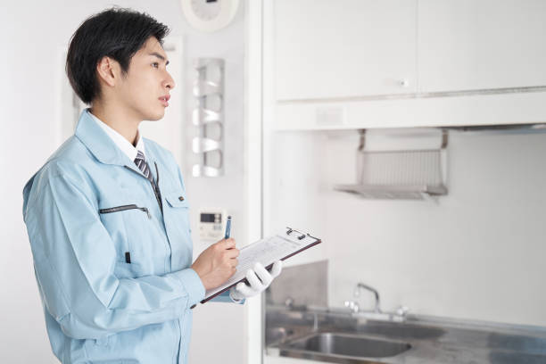 部屋の中の機器をチェックする日本人男性労働者 - people of color ストックフォトと画像