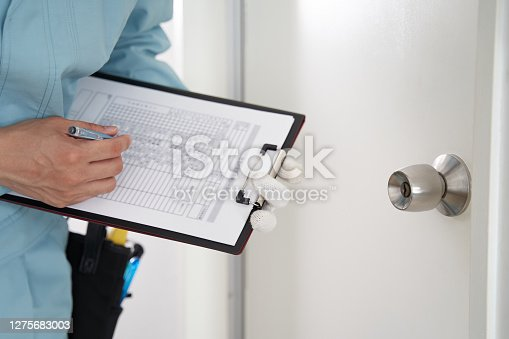 A Japanese male worker checks the locks on a house