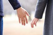 冬の公園で手をつないでいる日本人男女