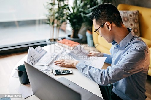 Japanese man with eyeglasses siting on floor in the living room and using smart phone and laptop for managing home finances