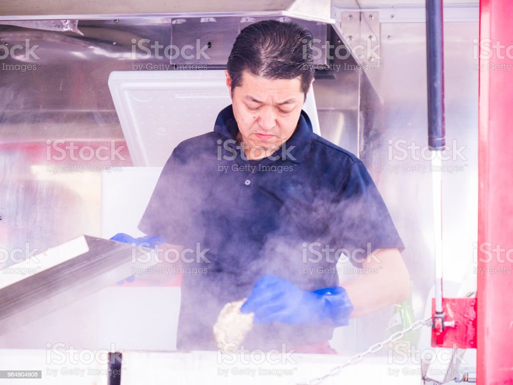 Japanese man cooking at the food truck. royalty-free stock photo