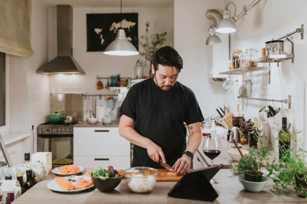 l'uomo giapponese taglia il salmone fresco mentre guarda il tablet digitale - cucinare foto e immagini stock
