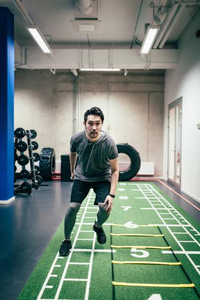 japanese man does cross training - runner rehab gym foto e immagini stock