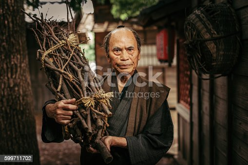 Japanese Man in traditional clothes carrying firewood