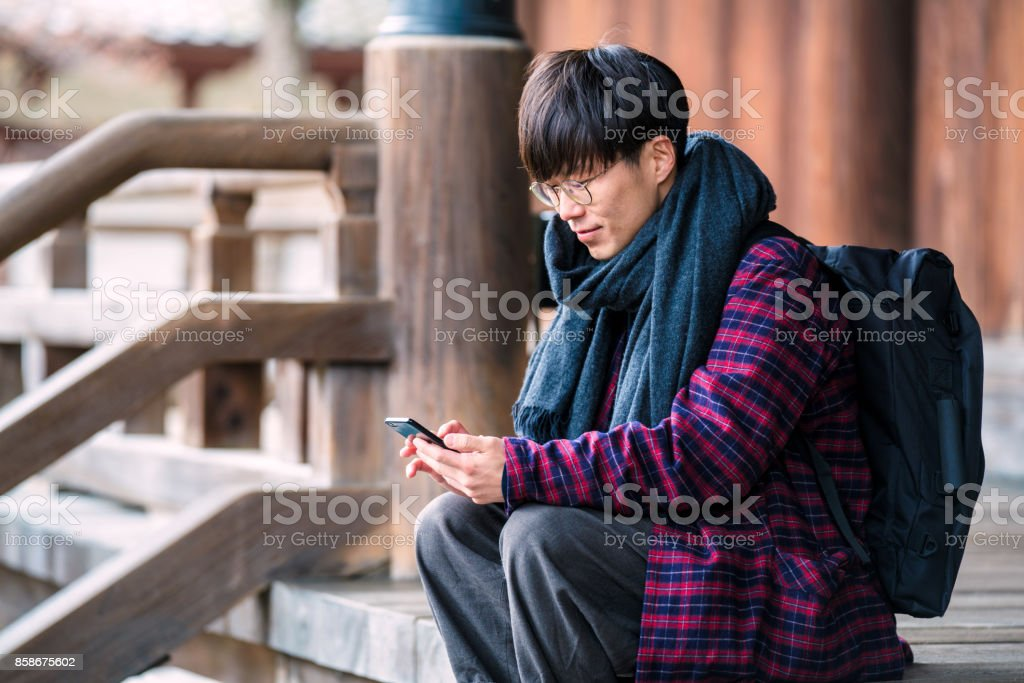 Japanese man is using a phone at Hyakumanben Chionji Temple stock photo