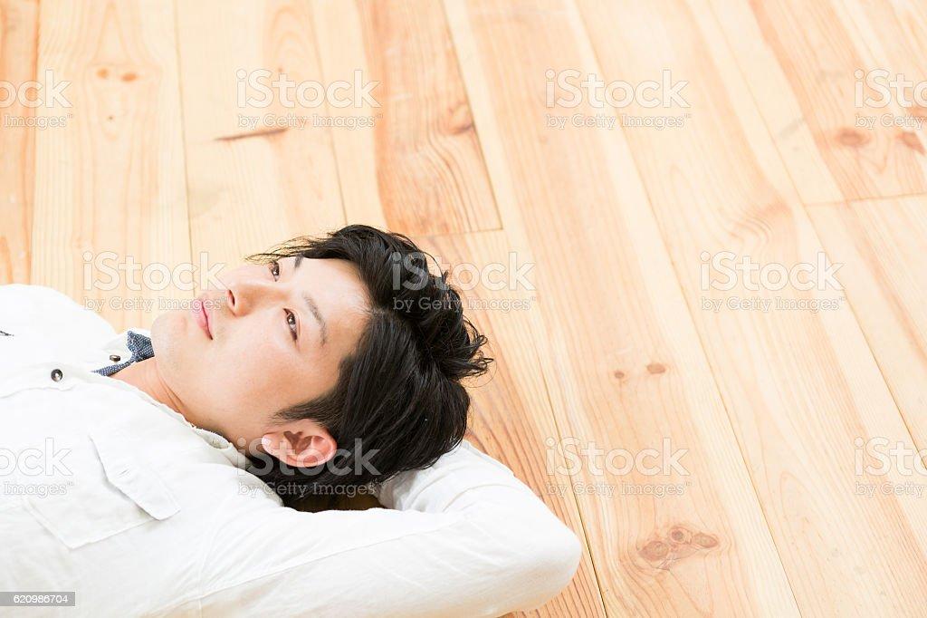 Japanese man lying down on flooring foto royalty-free