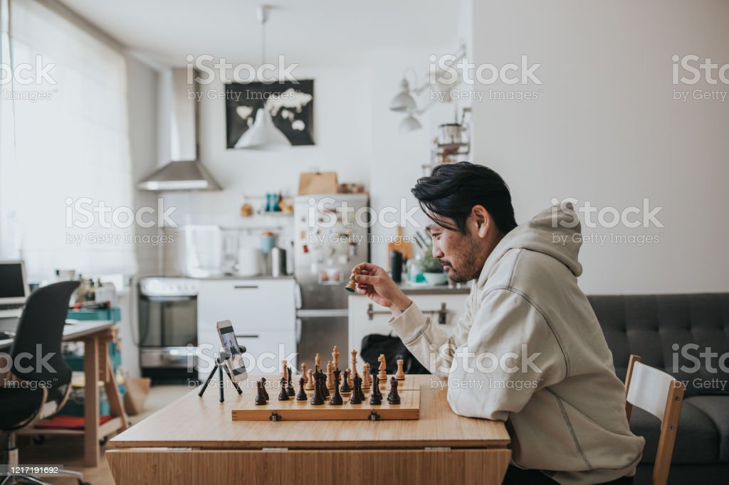 Japanese man playing virtual chess with friend online during social distancing times - Foto stock royalty-free di 35-39 anni