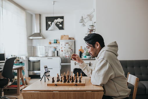 Japanese Man Playing Virtual Chess With Friend Online During Social Distancing Times Stock Photo - Download Image Now
