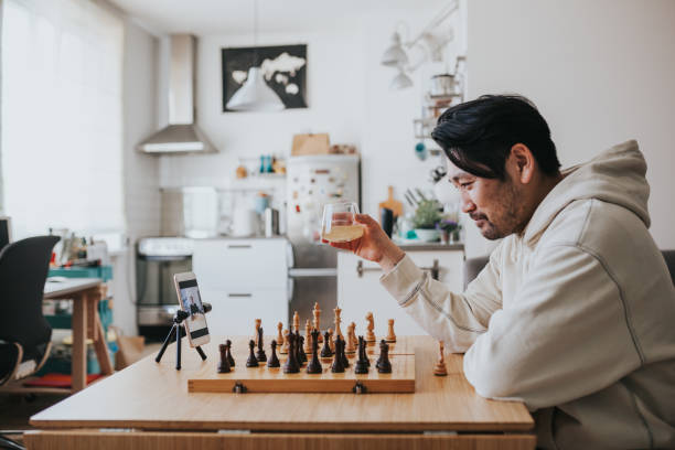 Japanese man playing virtual chess with friend online during social distancing times stock photo