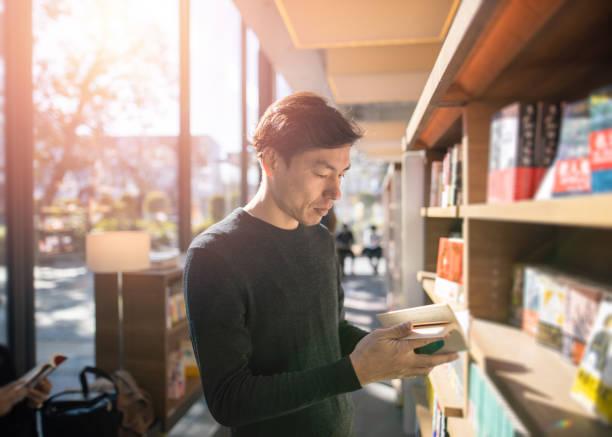 Japanese man reading book at library Japanese man reading book at library bookstore stock pictures, royalty-free photos & images