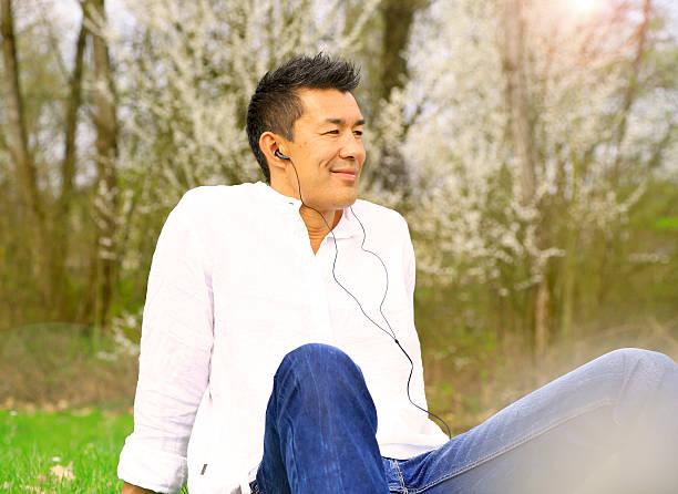 japonais homme se détendre et écouter de la musique sur le gazon - technique photographique photos et images de collection