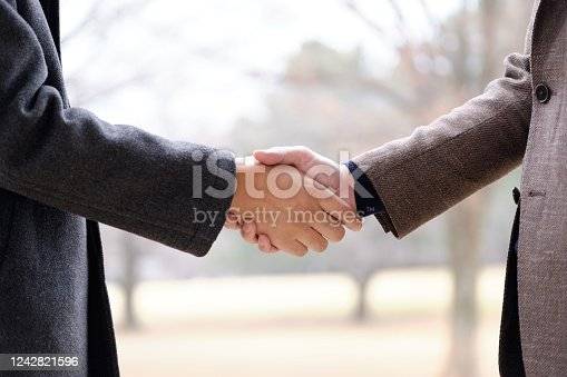 A Japanese man shaking hands outdoors.