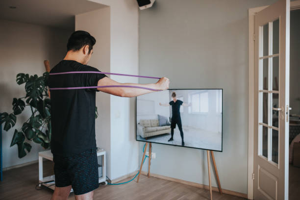 japanese man taking online fitness lessons during lockdown in isolation - exercise at home stock pictures, royalty-free photos & images