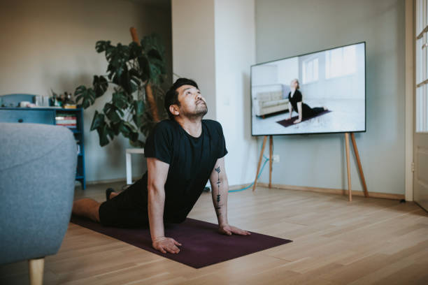 Japanese man taking online yoga lessons during lockdown in isolation Photo series of stay-at-home fitness during lockdown in self isolation. yoga instructor stock pictures, royalty-free photos & images