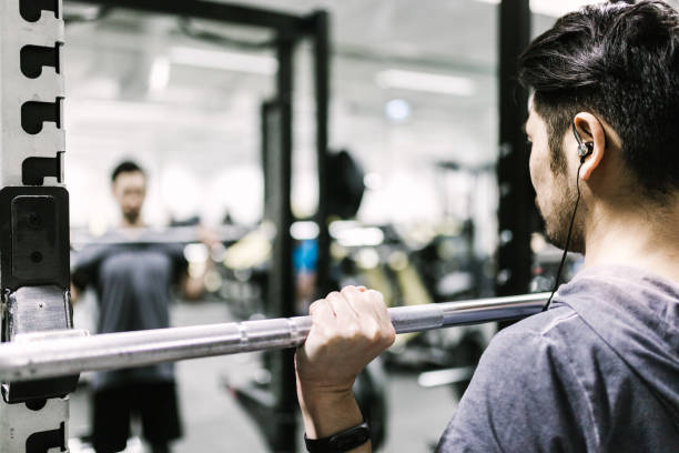 japanese man trains with barbell in the gym - runner rehab gym foto e immagini stock