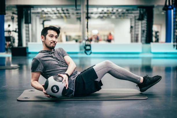 Japanese man trains with medicine ball stock photo