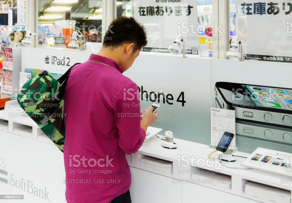 Japanese Man trying a White iPhone stock photo