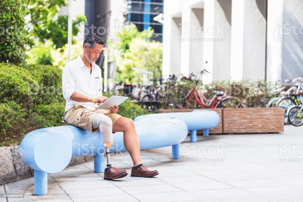 Japanese man using a digital tablet at a public park near some bike stand stock photo