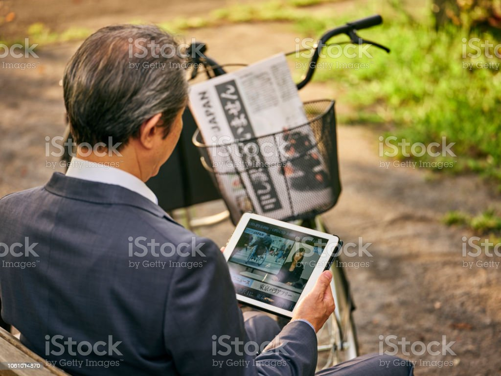 Japanese Man watching Online News stock photo