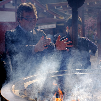 Japanese man waving famous holy smoke from a special bowl incense burner over his body at the old Asakusa Kannon Sensoji temple in the heart of Tokyo.