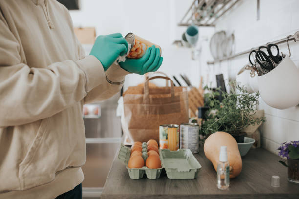 japanese man wearing protective gloves and cleaning canned food with wet wipes - grocery home foto e immagini stock