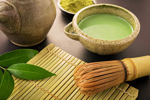 Japanese matcha accessories and green tea in bowl