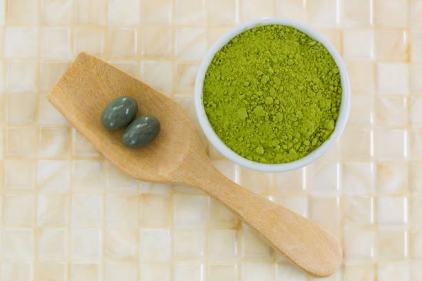 japanische matcha-grüntee-pulver, extrahierten grüntee konzentrat in weichen gel ergänzung kapsel - grüner tee kapseln stock-fotos und bilder